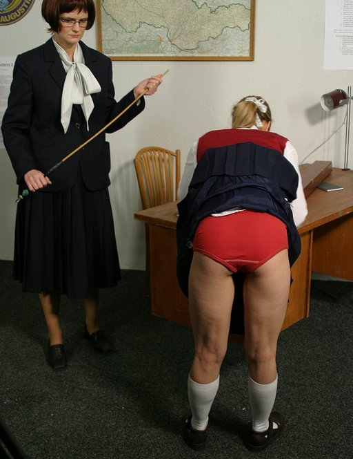 school mistress -- or is she a secretary? -- prepares to cane two naughty students