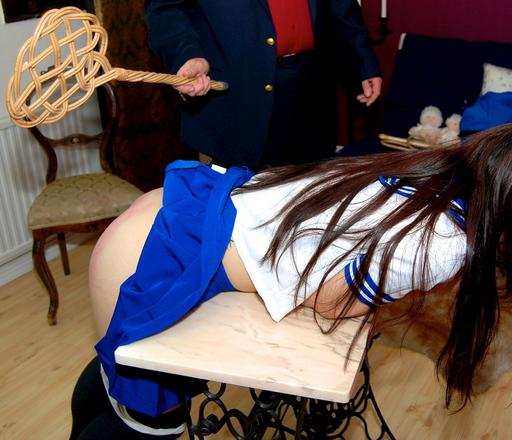 bent over and receiving a spanking with a carpetbeater
