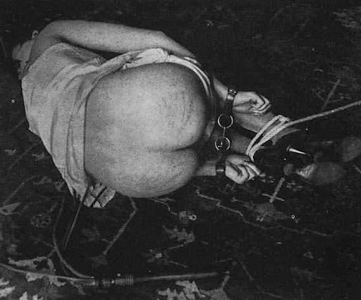 woman lying in bondage after being whipped with a martinet