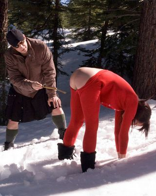 Nina bent over in the snow for a caning on her cold bare bottom
