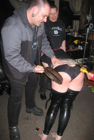 men pretend to spank her with a cast iron frying pan