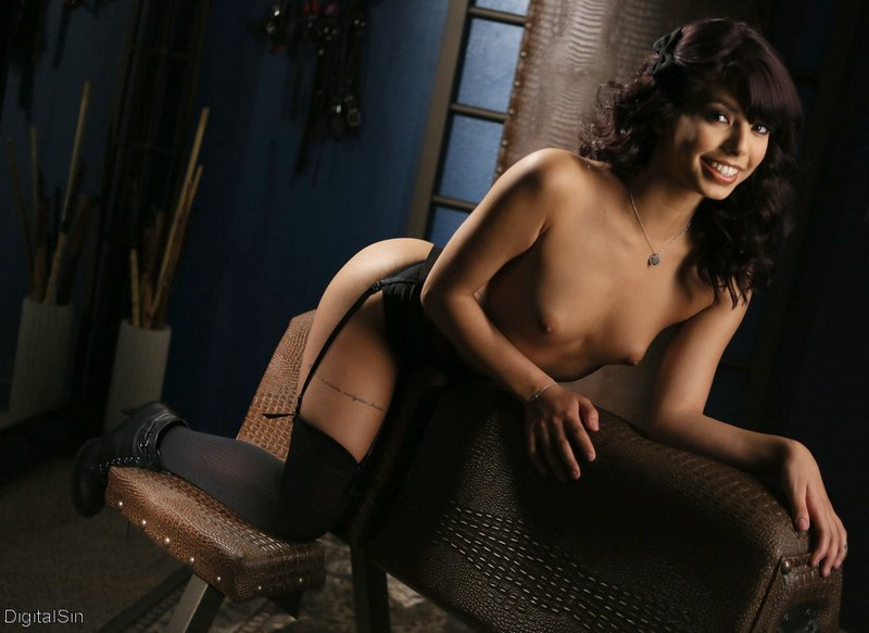 gina valentina on a spanking bench smiling by a bucket of canes