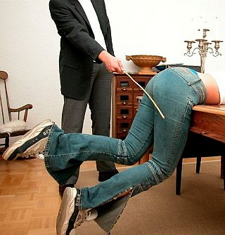 girl in tight denim kicking during spanking
