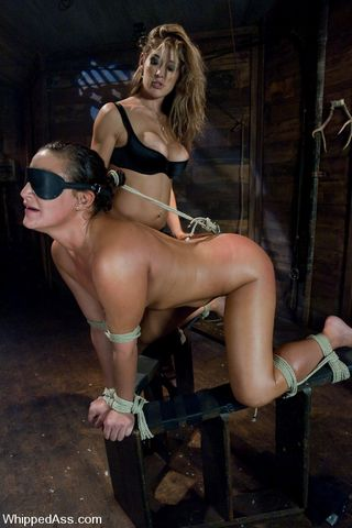 restrained with her hair tied to a butt hook via a very short rope