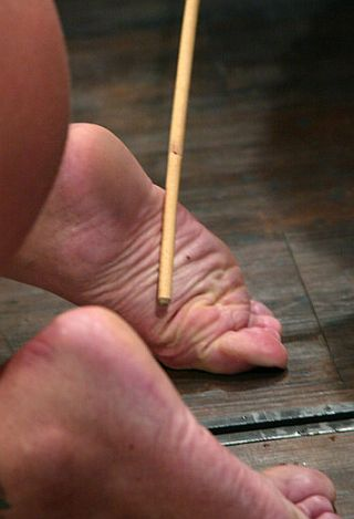 girl getting her feet caned