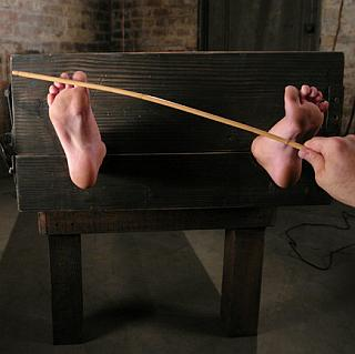 holly wellin gets her toes caned and tickled in the stocks
