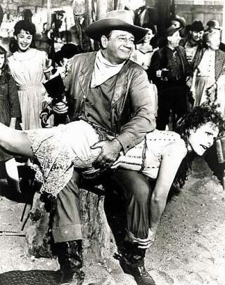 production still from McClintock showing John Wayne Spanking Maureen O'Hara