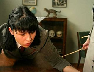 unhappy pouting face of girl getting a caning