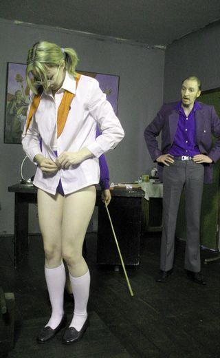 school girl slowly begins to take off her clothes for her caning