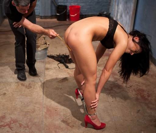Adrianna Chechik bent over with her panties around her ankles being caned