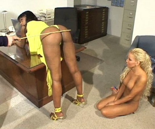 statuesque amazon black girl in amazing yellow dress gets caned as her little blonde co-worker kneels naked and watches