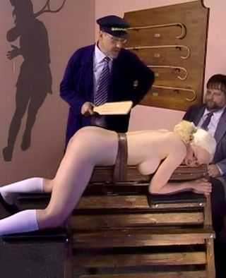 blonde strapped to a wooden horse and paddled hard