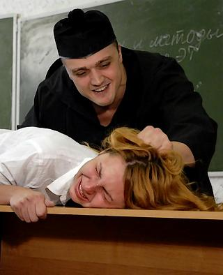 brutal Russian instructor leers over the crying face of a severely punished Russian school girl