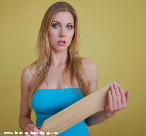 woman holding the big wooden paddle that\'s about to be used on her ass