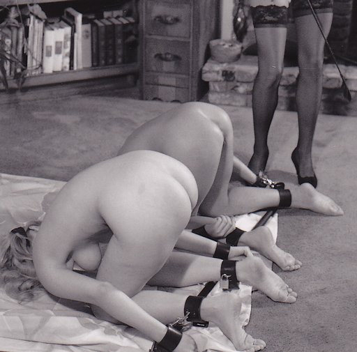 two girls on a spreader bar waiting for their riding crop whipping