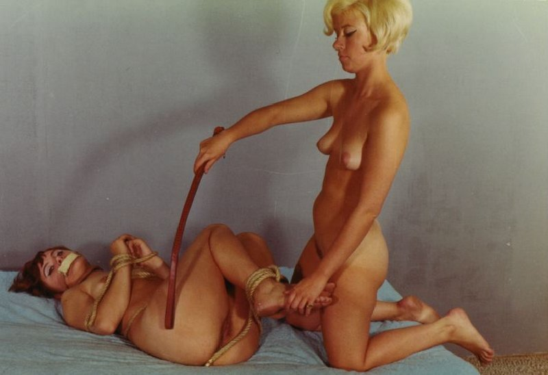blonde with a leather strap spanks a tape-gagged cutie who is not really tied up in tangles of heavy rope