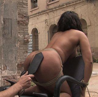 public spanking in a courtyard