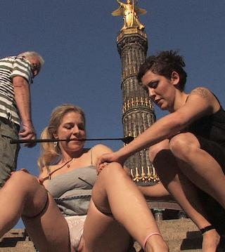 squatting on public steps in Berlin with riding crop in mouth while onlookers gape