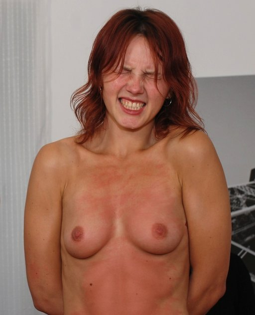 anguished face of a girl getting a breast whipping