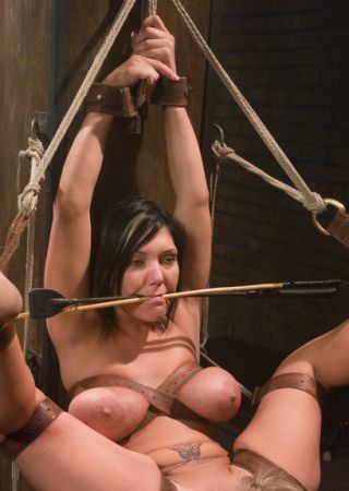 holding a cane and a crop in her mouth while another slavegirl is in position to lick her pussy