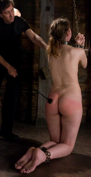 Kristine kneeling in chains for a spanking with a leather riding crop