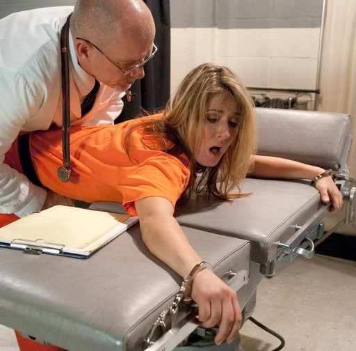 "Menacing prison doctor bends over a helpless handcuffed female inmate and tells her about the spanking and ""intimate exam\"" she\'s about to get"