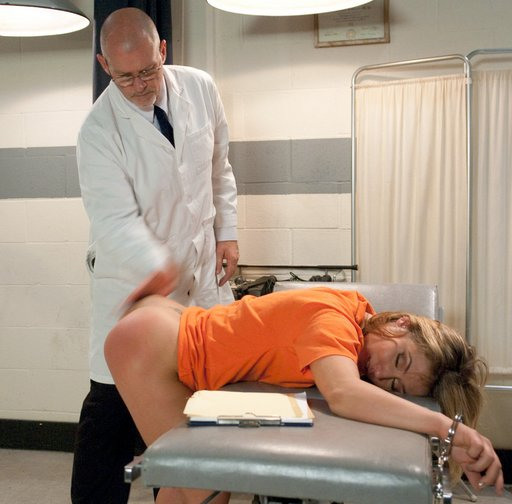 pretty female inmate is smiling as the brutal prison doctor gives her a hard spanking
