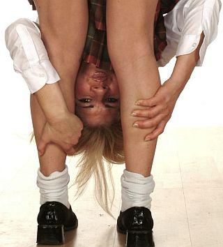 very FLEXIBLE schoolgirl bent over for caning and peering back between her legs