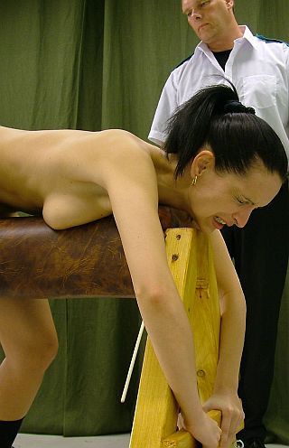 girl in pain and getting caned over a spanking horse