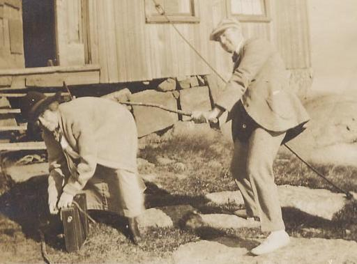 vintage postcard scene of a man spanking a woman with a big stick as she bends over her luggage