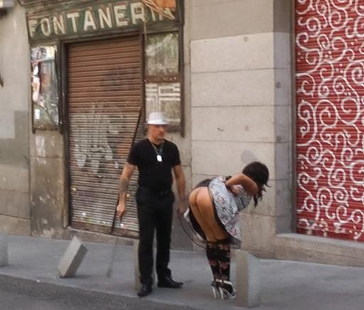 bent over for a riding crop spanking in the public street