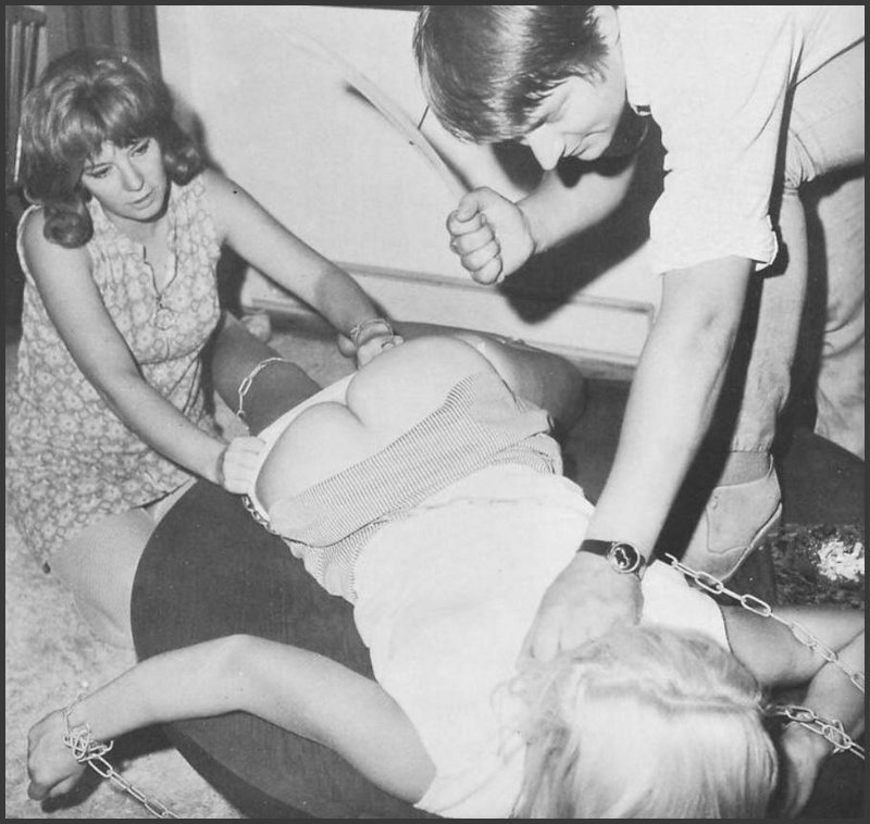 chained blonde being spanked with a wooden coat hanger