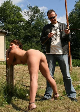 she is tied to the post as he inspects the switch
