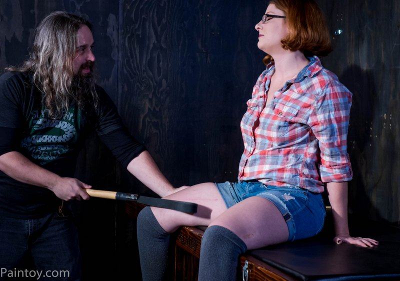 spanking her inner thighs with a leather strap