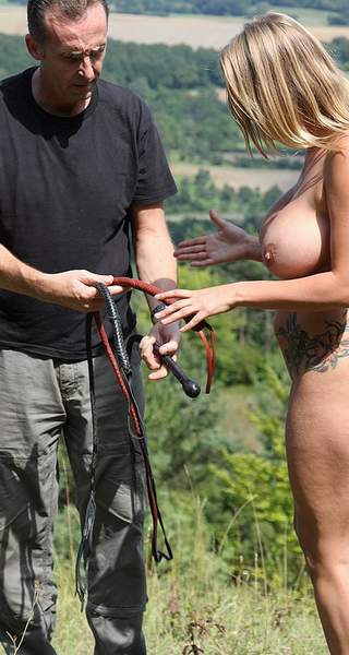 girl to be whipped in the sunshine chooses her whip from several on offer