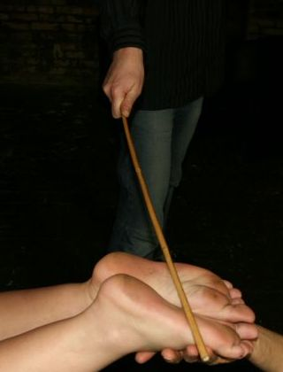 woman being caned on the soles of her feet