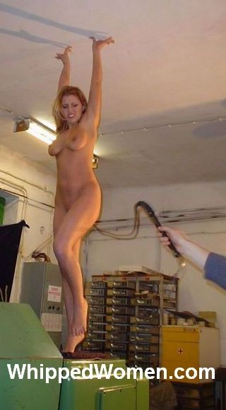 woman perched on tall object and being whipped