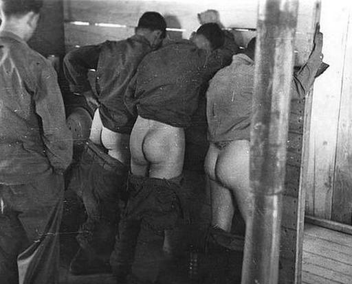 three young men in a washroom with their pants around their ankles