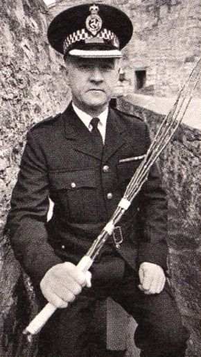 grumpy old officer holding a birch